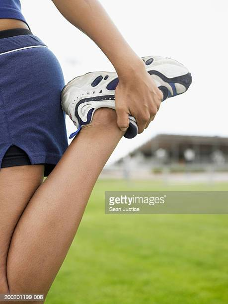 Teenage girl (14-16) stretching leg, low section, close-up