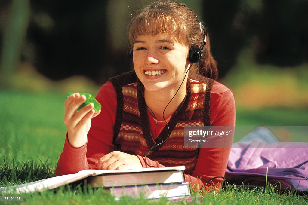 Teenage girl student lying down on lawn holding beeper