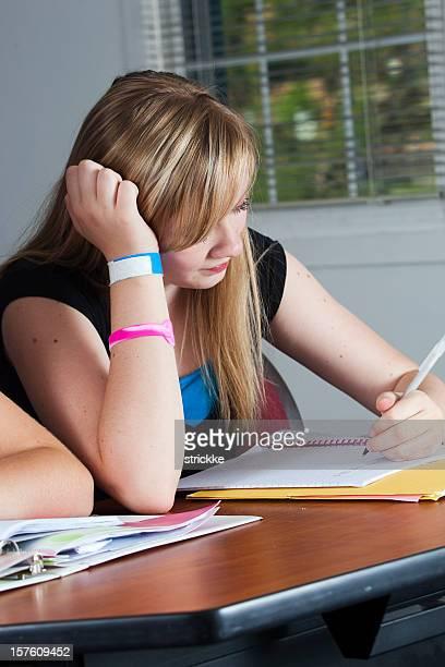 Teenage Girl Studies on Desk in Classroom Setting