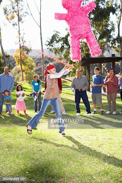 Teenage girl (12-14) swinging at pinata in park