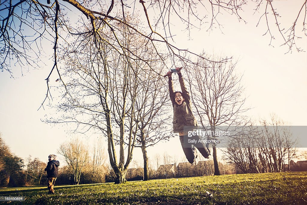 Teenage girl swinging on a rope swing : Stock Photo
