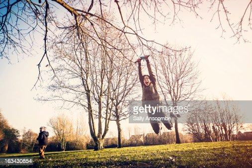 Teenage girl swinging on a rope swing : Stock Photo