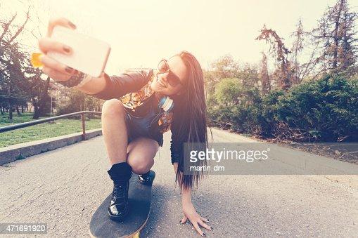 Jeune femme prenant un selfie sur un skate