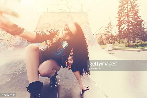 Teenage girl taking a selfie at a skateboard