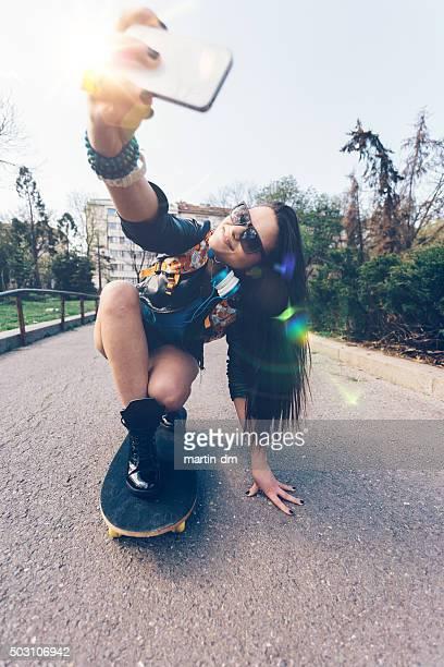 Menina adolescente tomando um selfie em um Skate