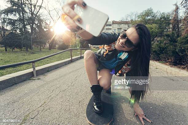 Teenage girl taking a selfie at a skateboard