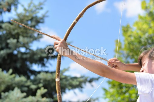 Teenage girl taking aim with a bow and arrow : Stock Photo