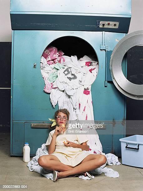 Teenage girl (16-18) taking break beside industrial washing machine