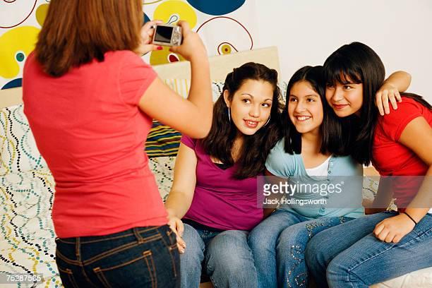 Teenage girl (14-15) taking digital picture of friends (12-13)