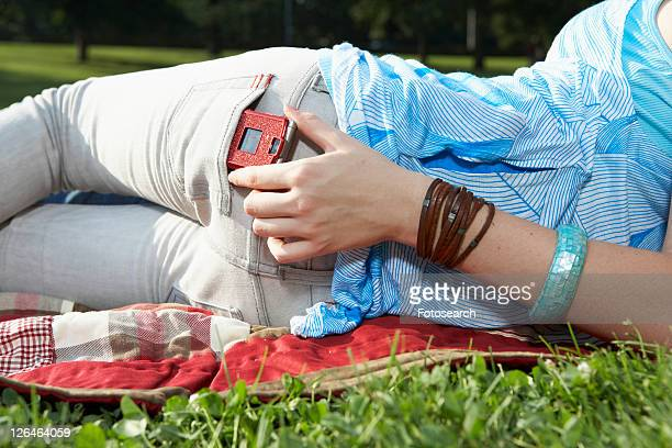 Teenage girl taking mobile phone from back pocket (midsection)