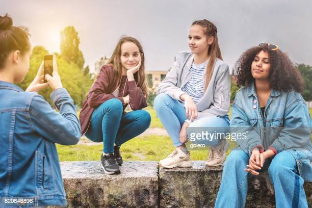 teenage girl taking photo of girlfriends