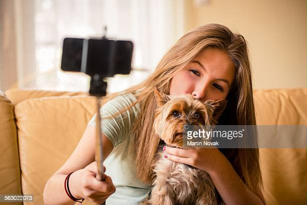 Teenage girl taking photo of herself and her dog w