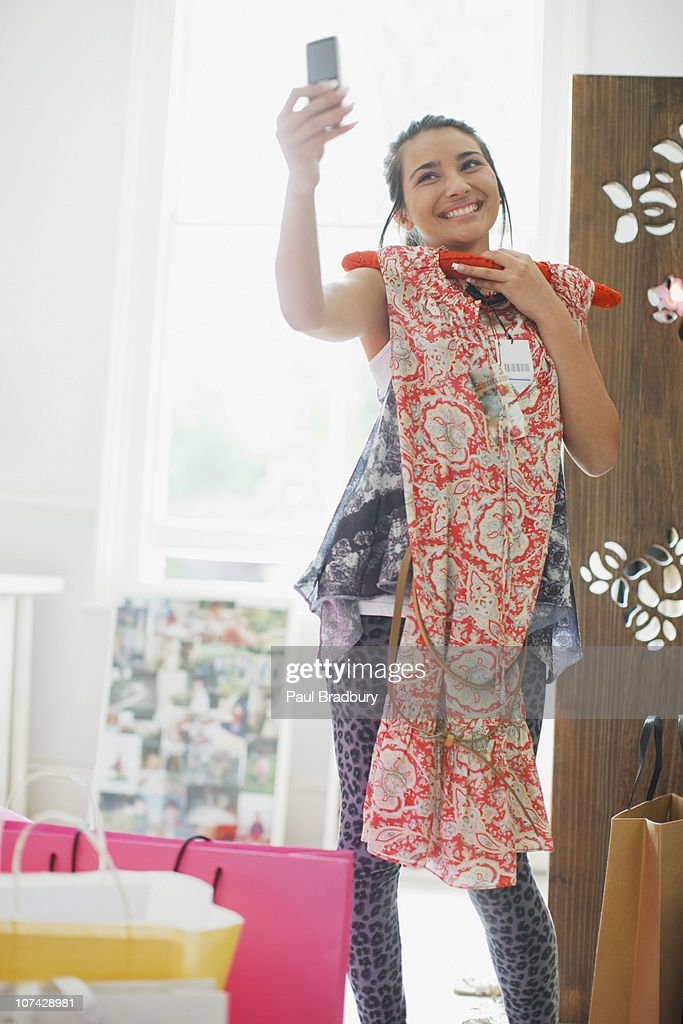 Teenage girl taking picture of dress with cell phone : Stock Photo