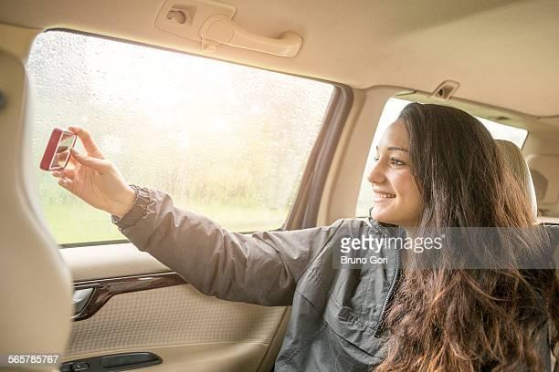 Teenage girl taking smartphone selfie in car back seat
