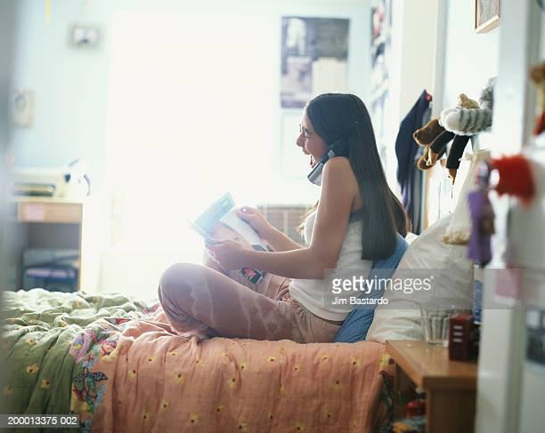 Teenage girl (12-14) talking on phone in bed room
