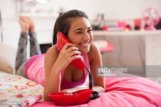 Teenage girl talking on telephone in bedroom