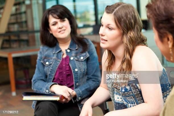 Teenage girl talking to adults in a group discussion setting