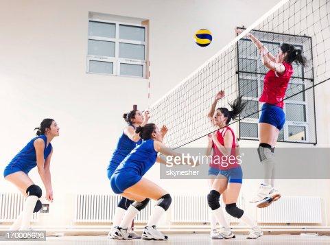 Teenage girl team playing volleyball.