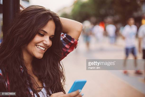 Teenage girl texting at the street