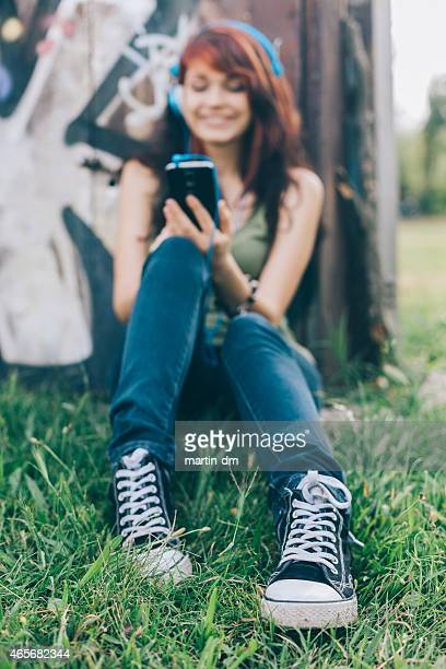 Teenage girl texting in the park