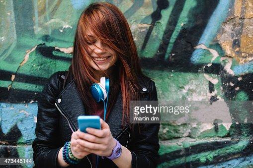Teenage girl texting on smartphone outside : Stock Photo