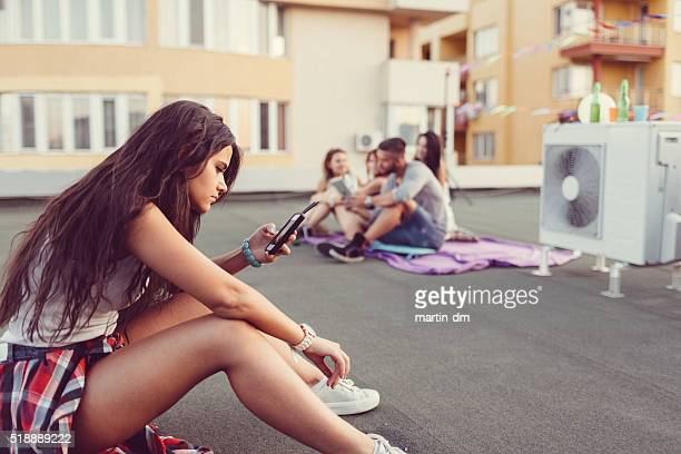 Teenage girl texting on the rooftop