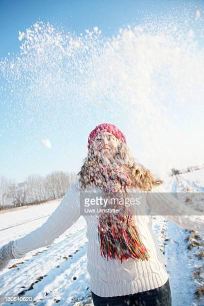 Teenage girl throwing snow up into the air