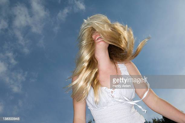 Teenage girl tossing her hair outdoors