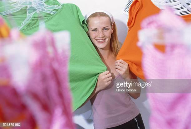 Teenage girl touching t-shirts in shop