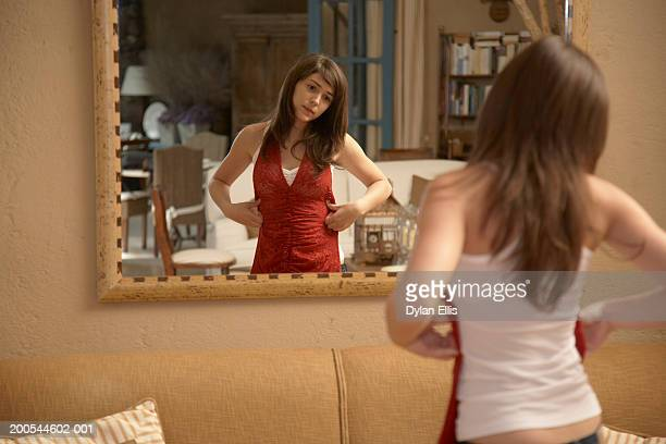 Teenage girl (16-18) trying clothes on in mirror