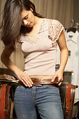 Teenage girl trying on a belt