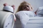 Teenage girl turning off alarm clock