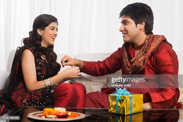 Teenage girl tying rakhi on her brother wrist