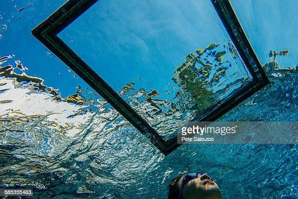 Teenage girl underwater, looking through frame on water surface