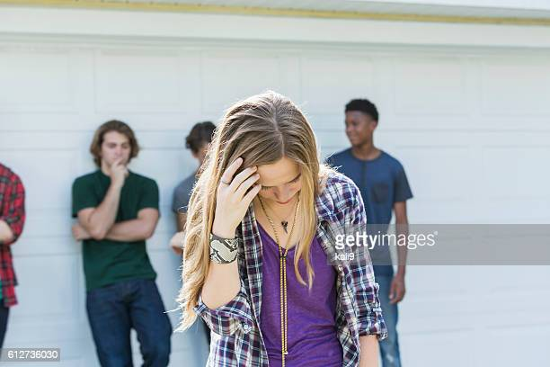 Teenage girl upset looking down, young men in background