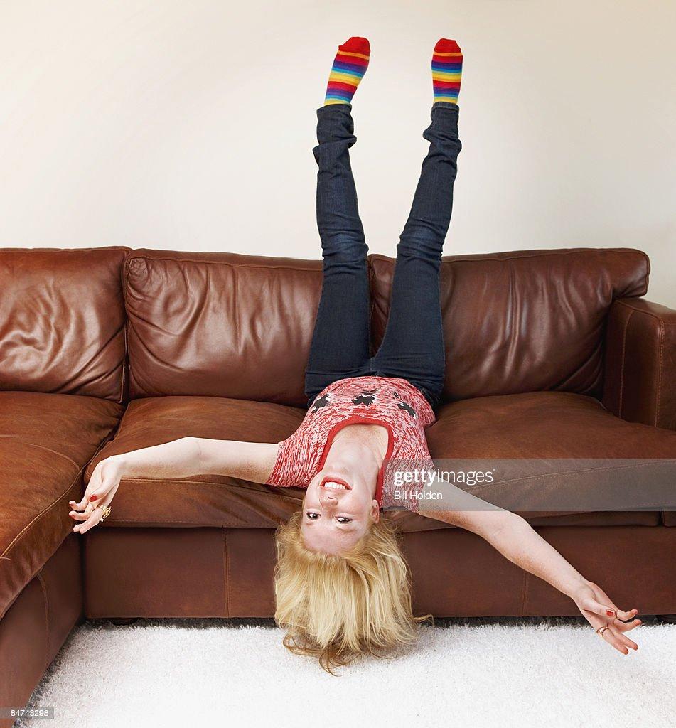 Teenage girl upside-down on sofa : Stock Photo