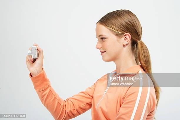 Teenage girl (13-15) using camera, profile