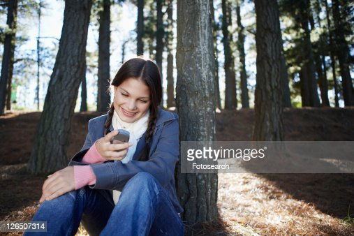 Teenage girl using cell phone in woods