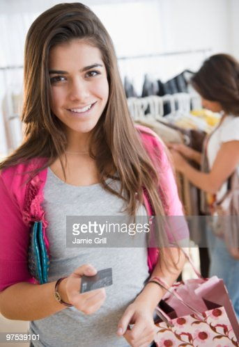 Teenage girl using credit card while shopping : Stock Photo
