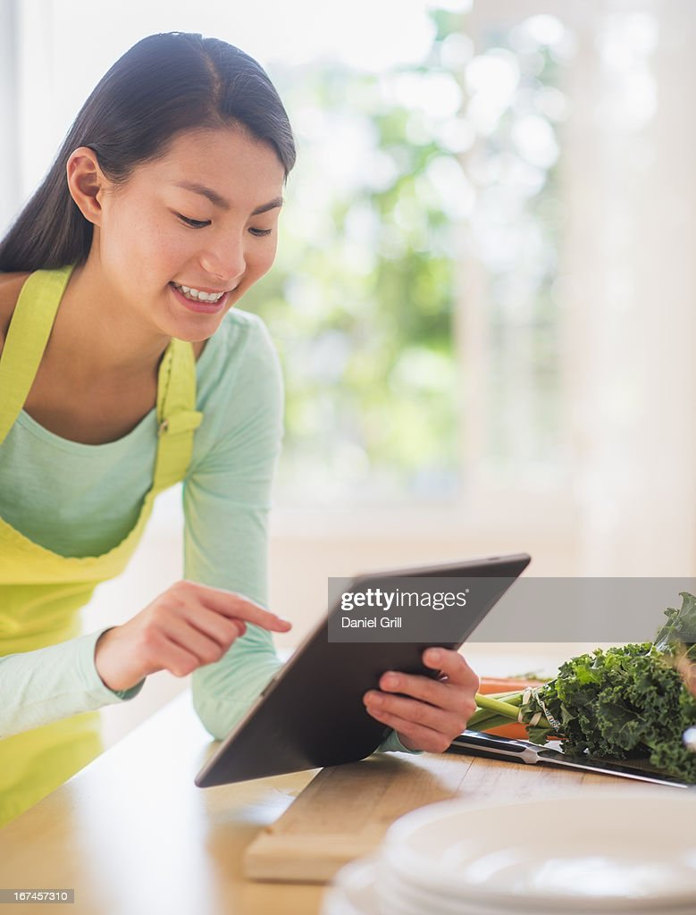 Teenage girl using digital tablet in kitchen : Stock Photo
