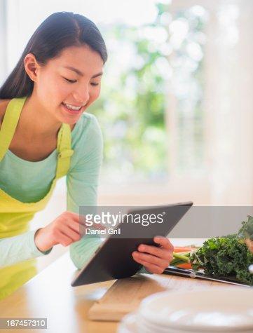 Teenage girl using digital tablet in kitchen : Stock Photo