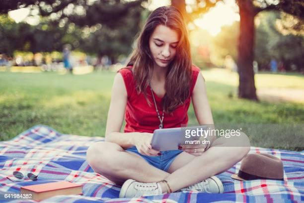 Teenage girl using digital tablet in the city park
