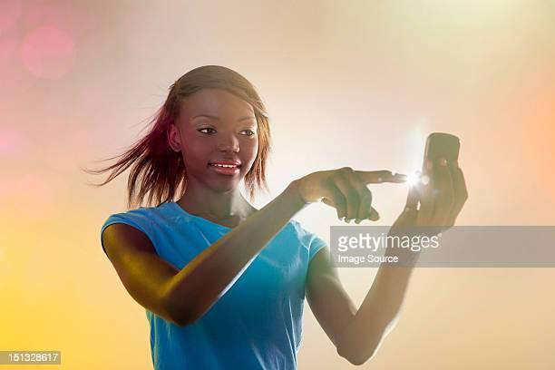 Teenage girl using illuminated cellphone