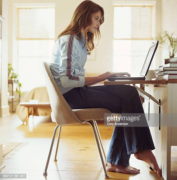 Teenage girl (14-16) using laptop at home, side view