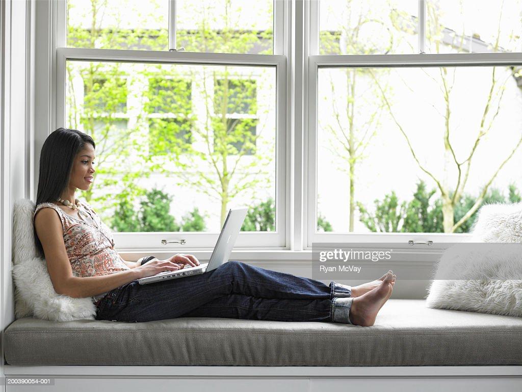 Teenage girl (15-17) using laptop on window seat, side view