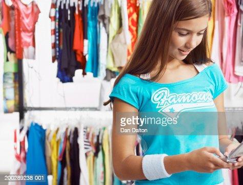 Similar images. Teenage Girl Holding Up Dress On Hanger In Change Room Of Shop
