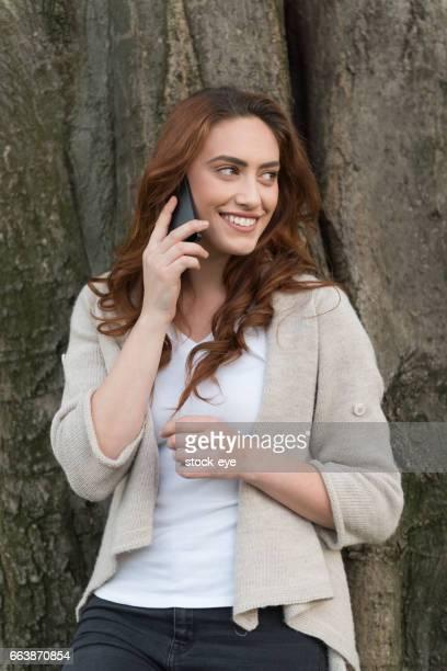 Teenage girl using phone in park
