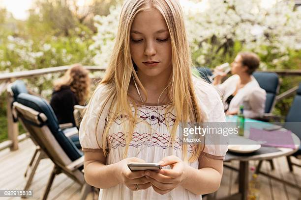 Teenage girl using smart phone at yard with family sitting in background