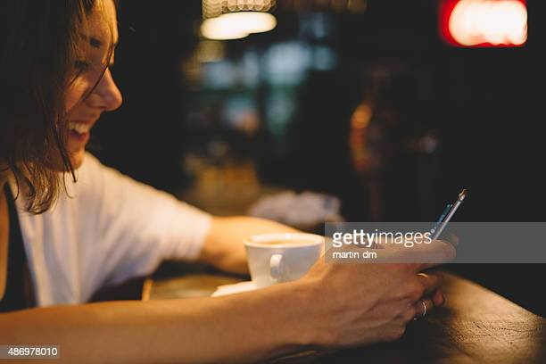 Teenage girl using smartphone in a cafe
