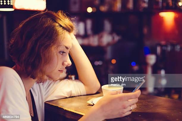 Adolescente usando teléfono inteligente en un café